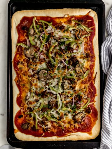 overhead view supreme pizza in square baking sheet with napkin and pizza cutter