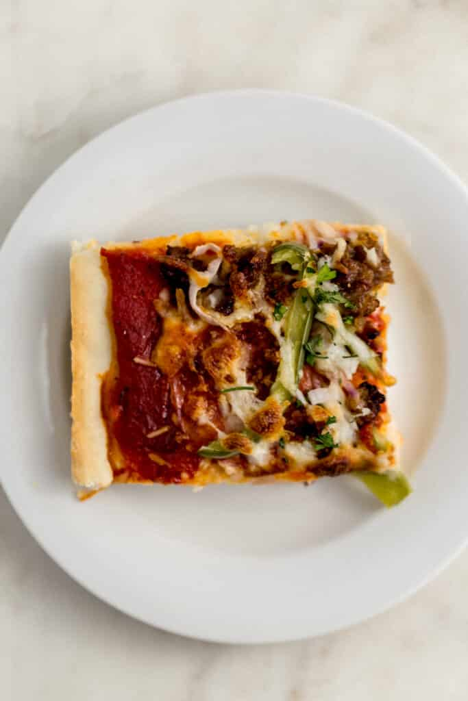 square piece of supreme pizza on white plate