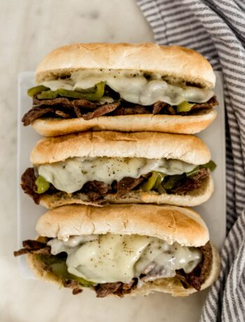 overhead view instant pot philly cheesesteaks on white square plate with napkin