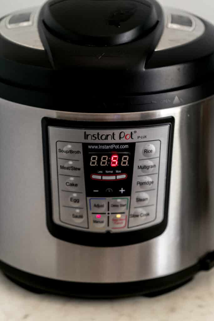 side view instant pot pressure cooker set to five minutes cooking time