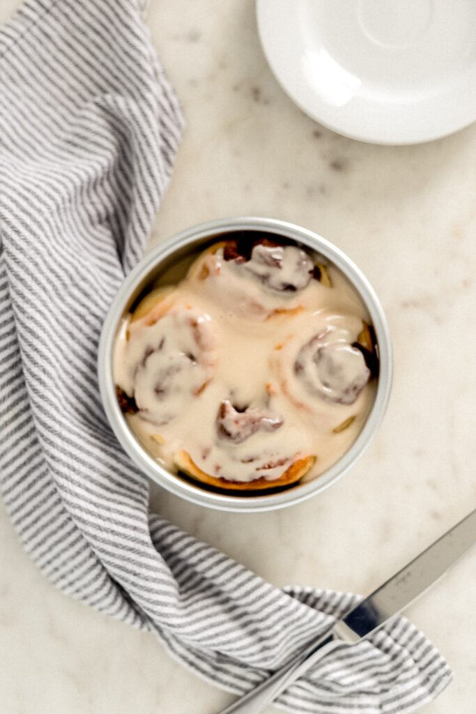 small batch cinnamon rolls in baking dish with napkin, plates, and knife