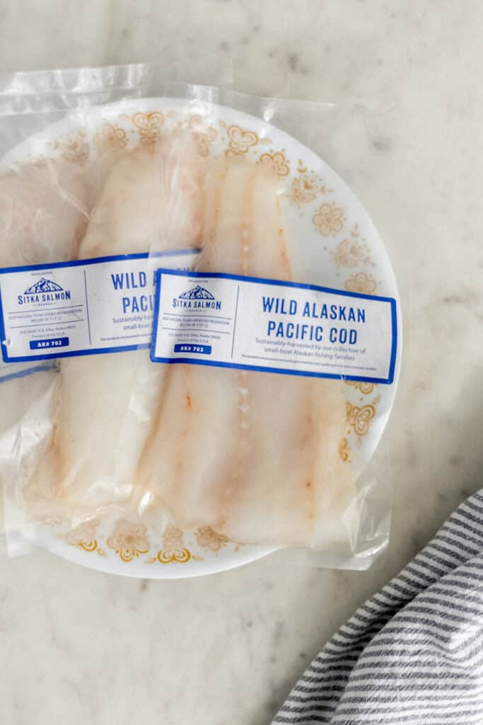 packets of fresh wild Alaskan Pacific cod in plastic on plate with napkin