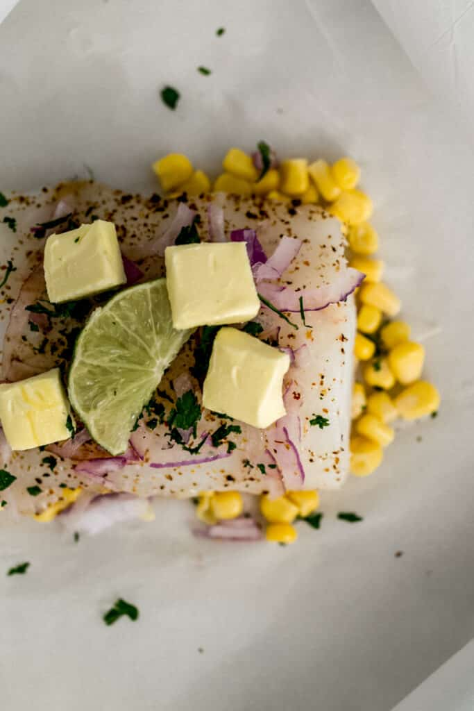 cod, corn, red onion, butter, lime on parchement paper