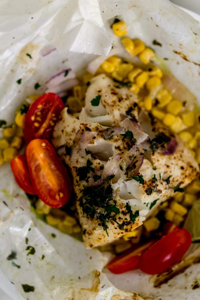 baked cod in parchment topped with sliced grape tomatoes