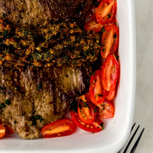 flank steak in square white baking dish topped with sun dried tomato pesto