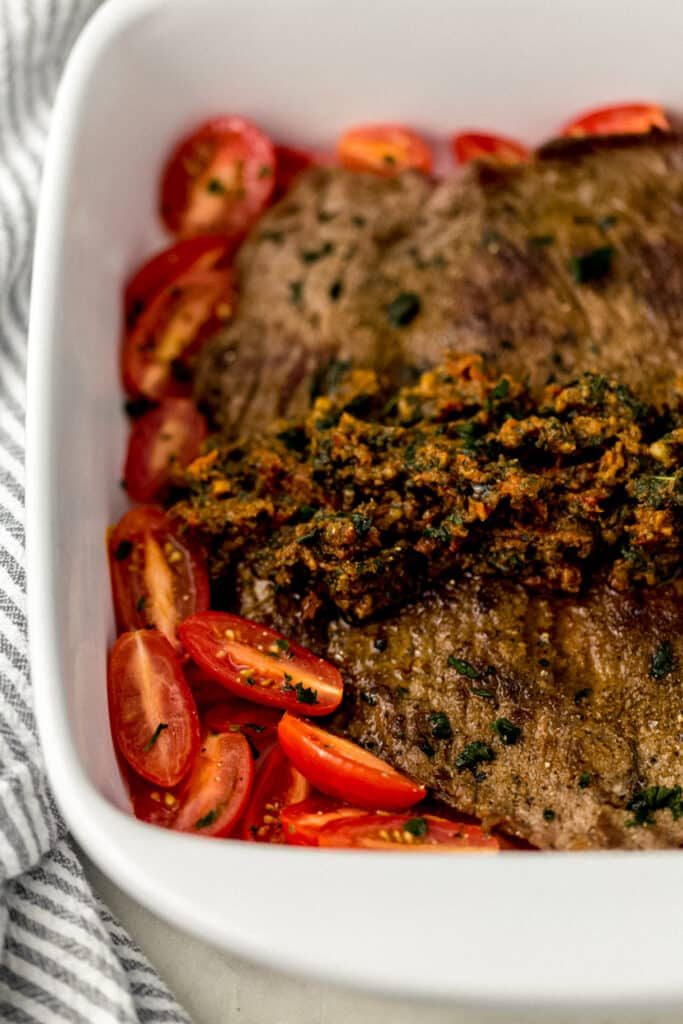 close up side view flank steak topped with pest in square white baking dish