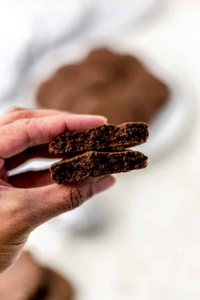 hand holding chocolate cookie cut in half