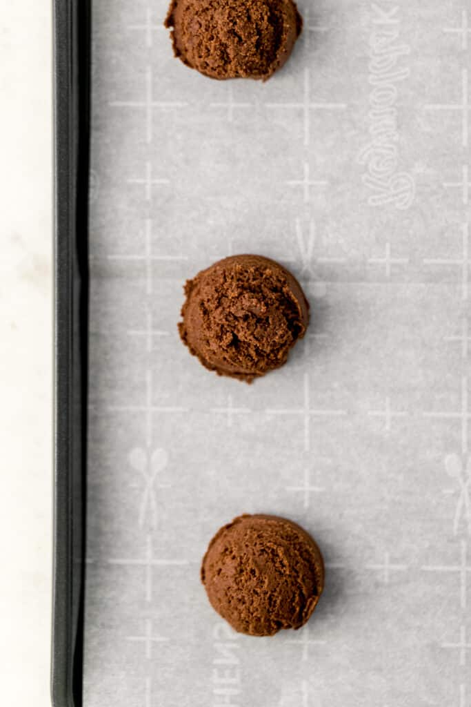 chocolate cookie dough scooped on parchment lined baking sheet before baking