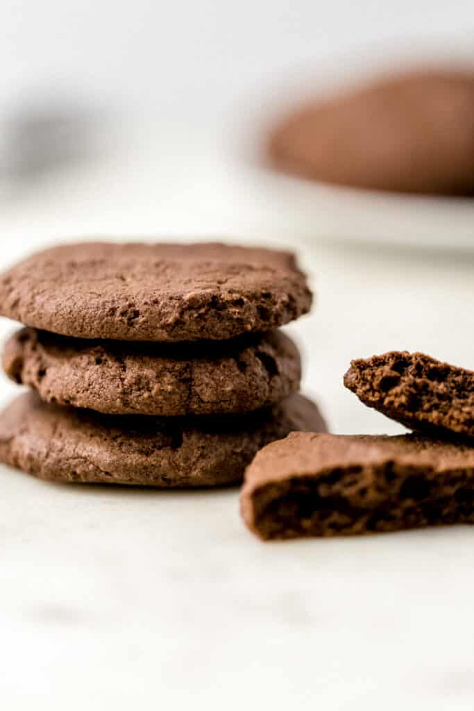 stack of three chocolate sugar cookies with a single cookie split in half on the side
