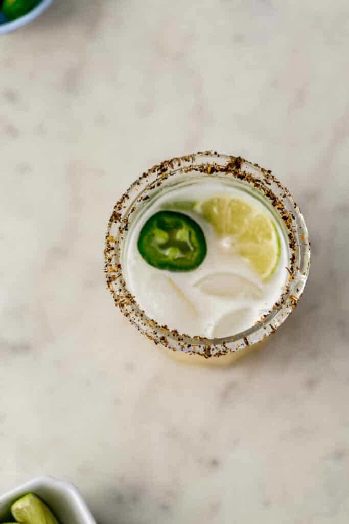 jalapeno margarita in a glass with jalapeno slices and lime
