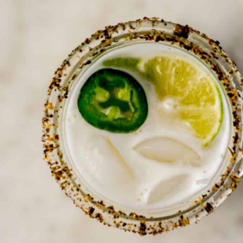 overhead view jalapeno margarita in a glass with jalapeno slices and lime