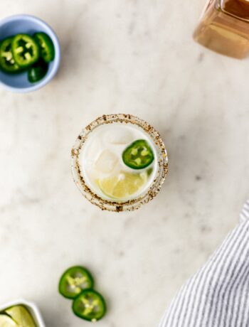 spicy margarita in a glass with jalapeno, lime, and cloth napkin