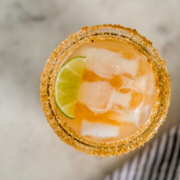 overhead view kombucha margarita with lime and ice in sugar rimmed glass.