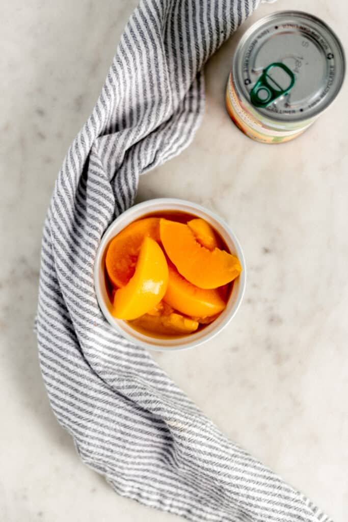 small white bowl with sliced cling peaches next to can of peaches