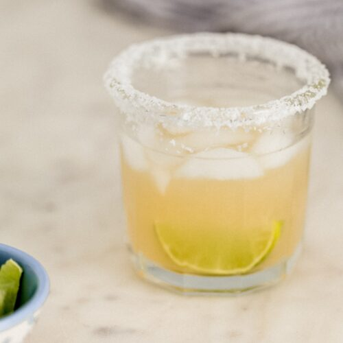 close up side view margarita in salt rimmed glass with small bowl of lime wedges