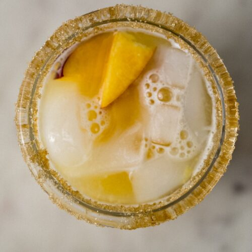 sugar rimmed glass with peach margarita on ice.