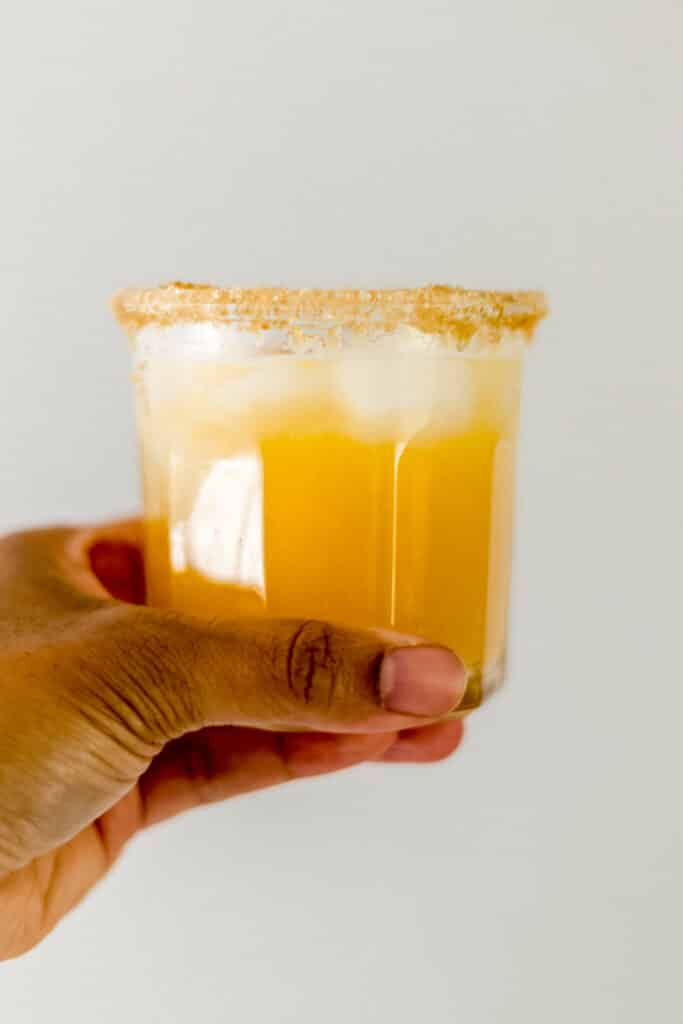 hand holding glass with peach margarita in it.