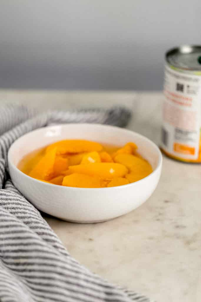 close up side view peaches in a white bowl with can of peaches next to it.