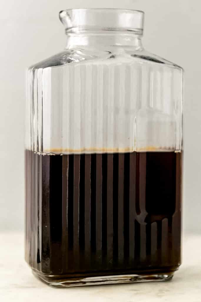 close up side view glass pitcher with black tea in it.