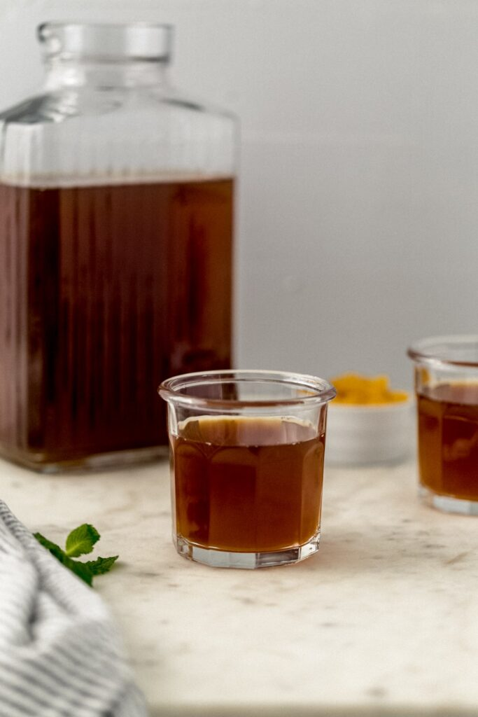 pitcher and two glasses with peach tea in them.