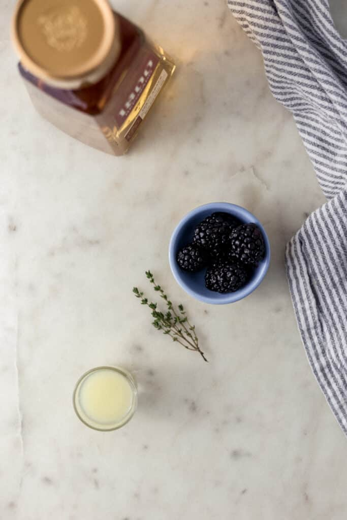 ingredients for blackberry thyme margarita with cloth napkin on marble surface