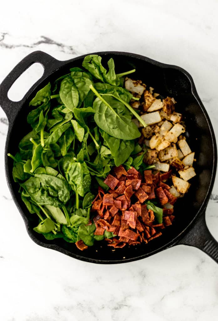 spinach and bacon with potato and onion in cast iron skillet