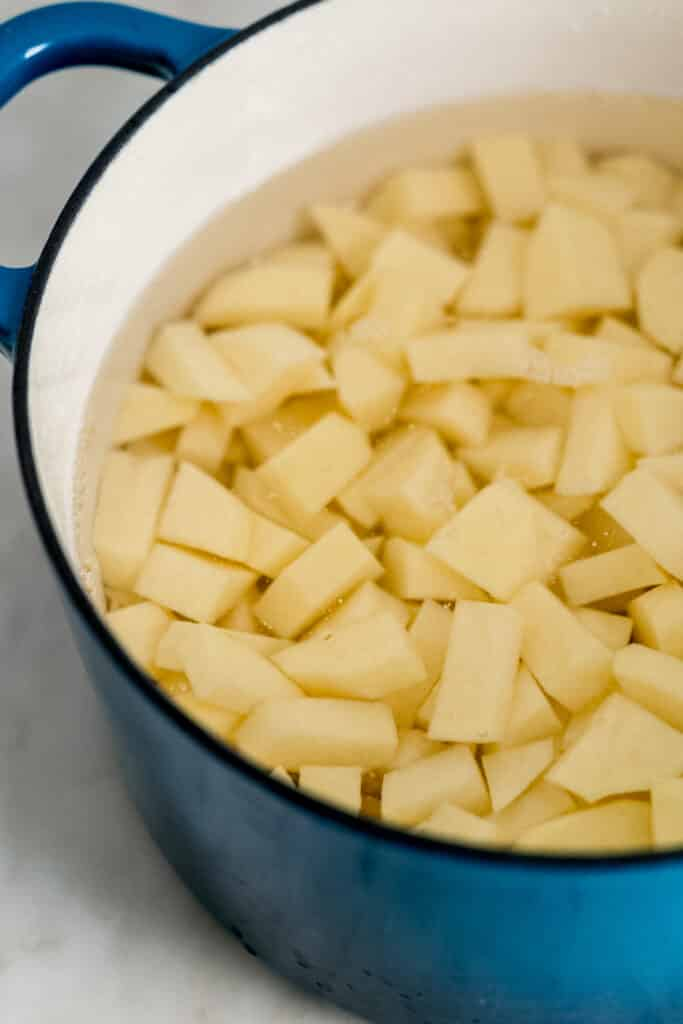 large pot with cut up potatoes in water in it.