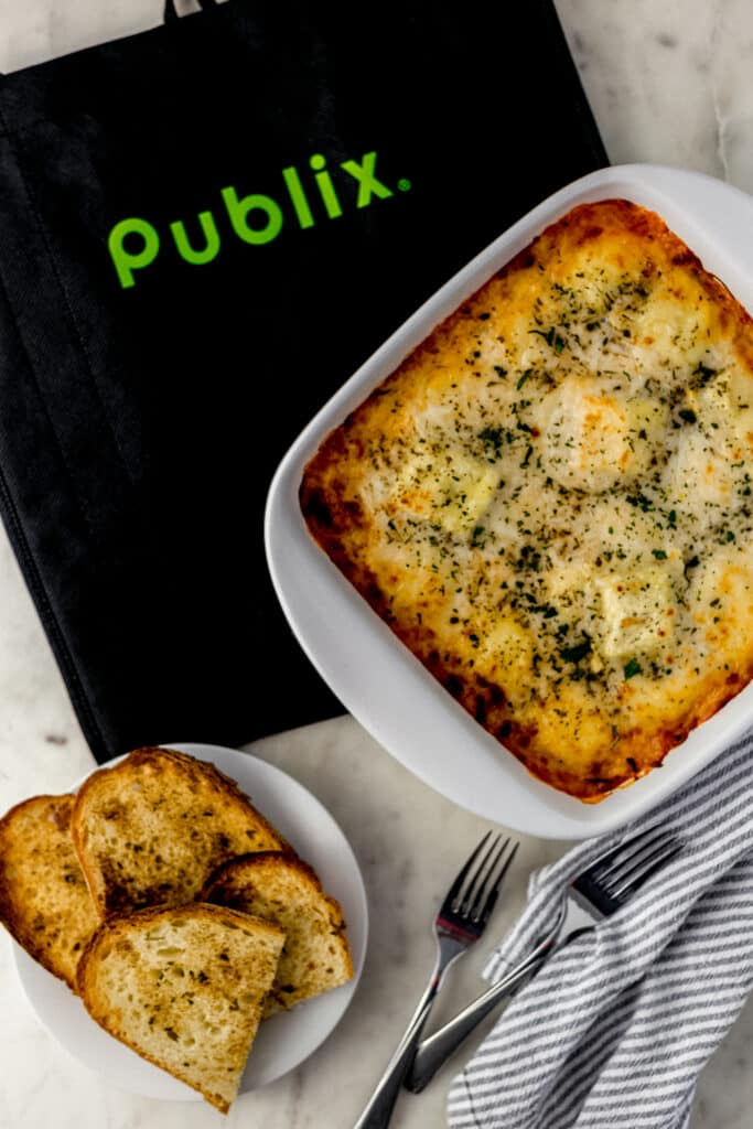 cheesy ravioli bake in square white baking dish with plate of garlic bread and grocery bag.
