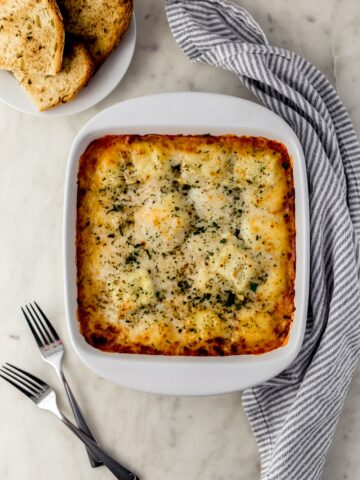 overhead of cheese ravioli bake in white baking dish with forks, cloth napkin, and white plate with garlic bread.