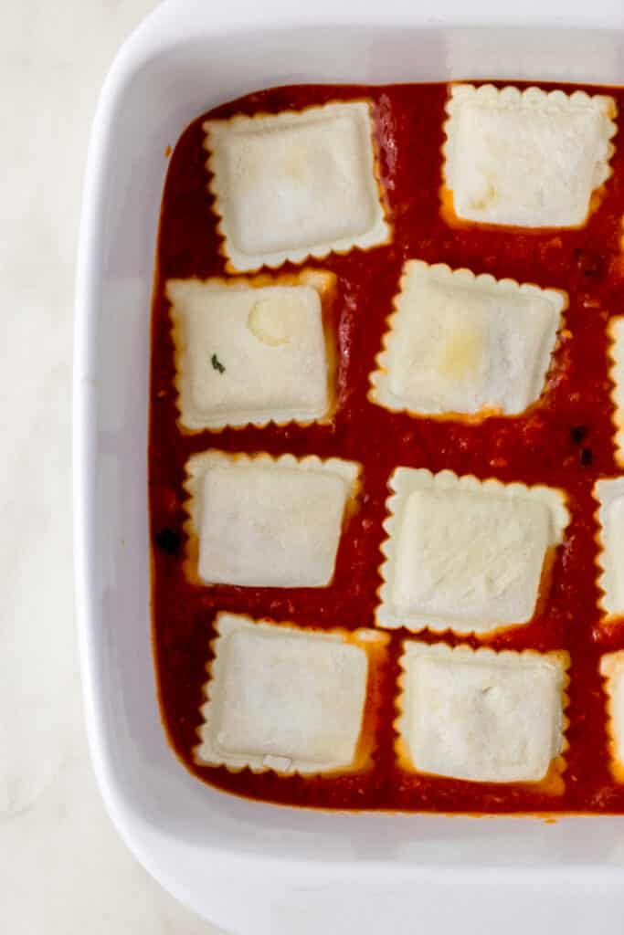 frozen ravioli and sauce in square white baking dish