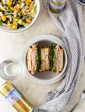 overhead view of sandwich in bowl, salad, drinks, and cloth napkin