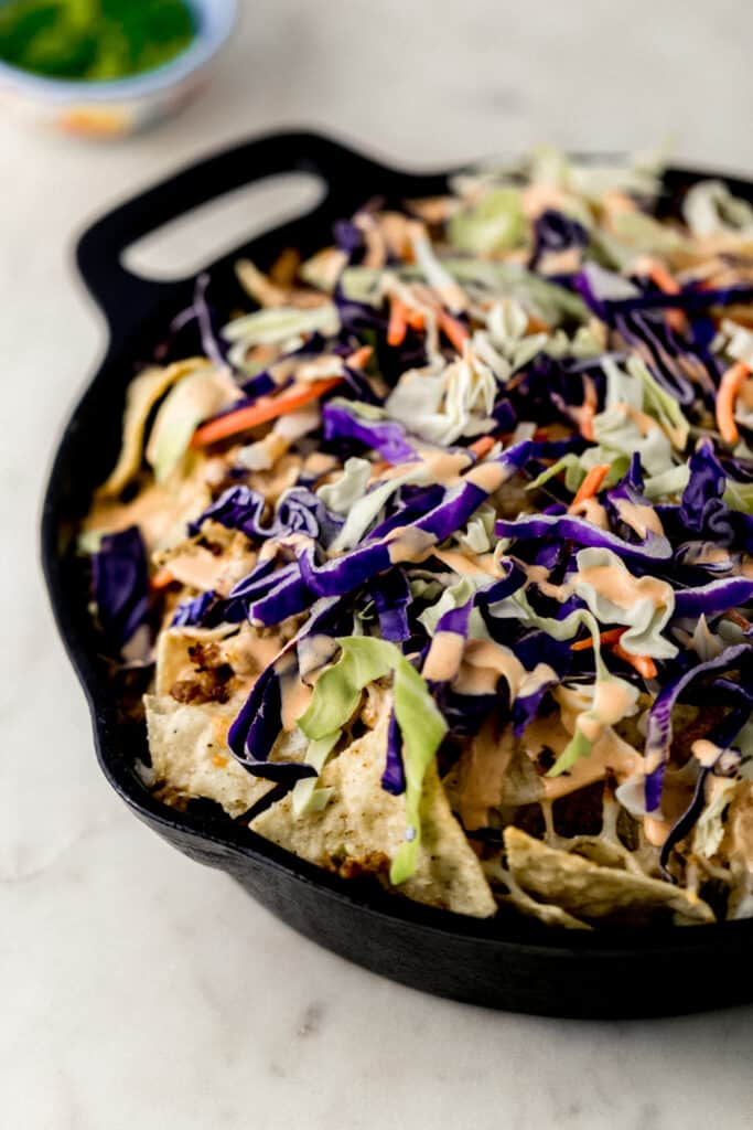 close up side view ground pork nachos in cast iron skillet topped with cole slaw and spicy mayo.