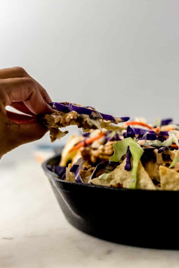 hands holding ground pork nachos over cast iron skillet