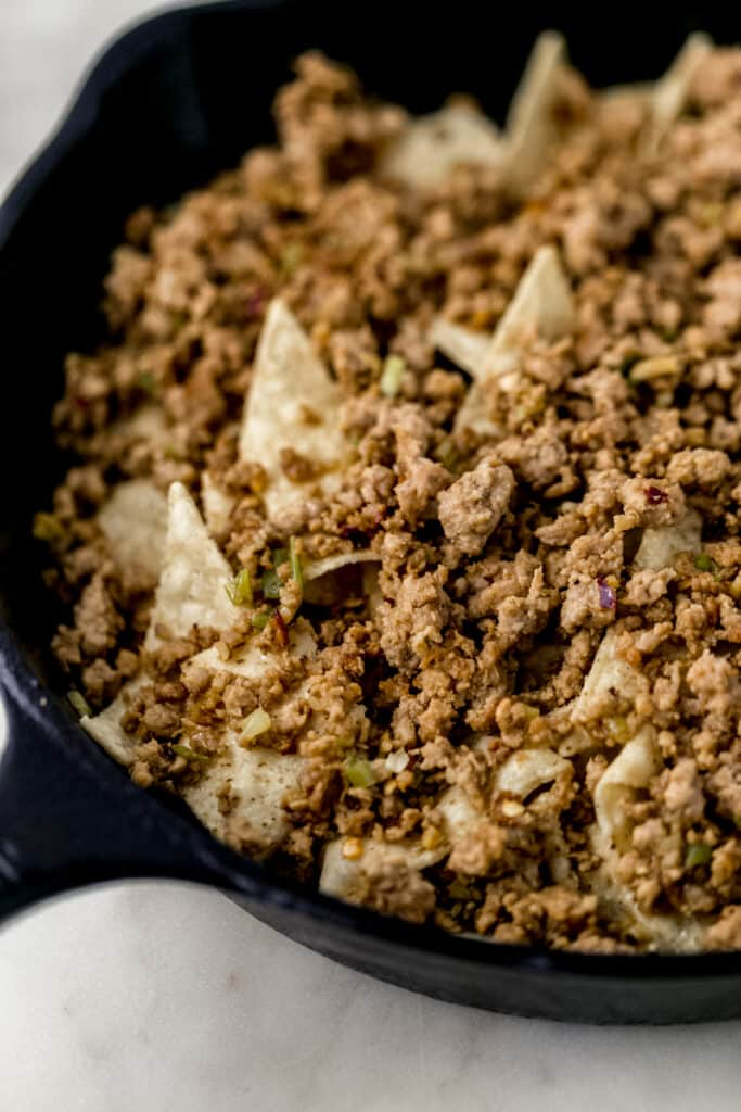 close up side view tortilla chips and ground pork in cast iron skillet