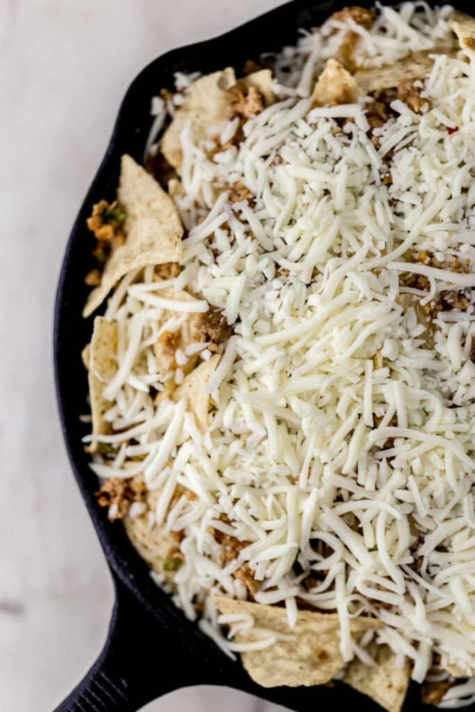 tortilla chips, ground pork, and mozzarella cheese in cast iron skillet