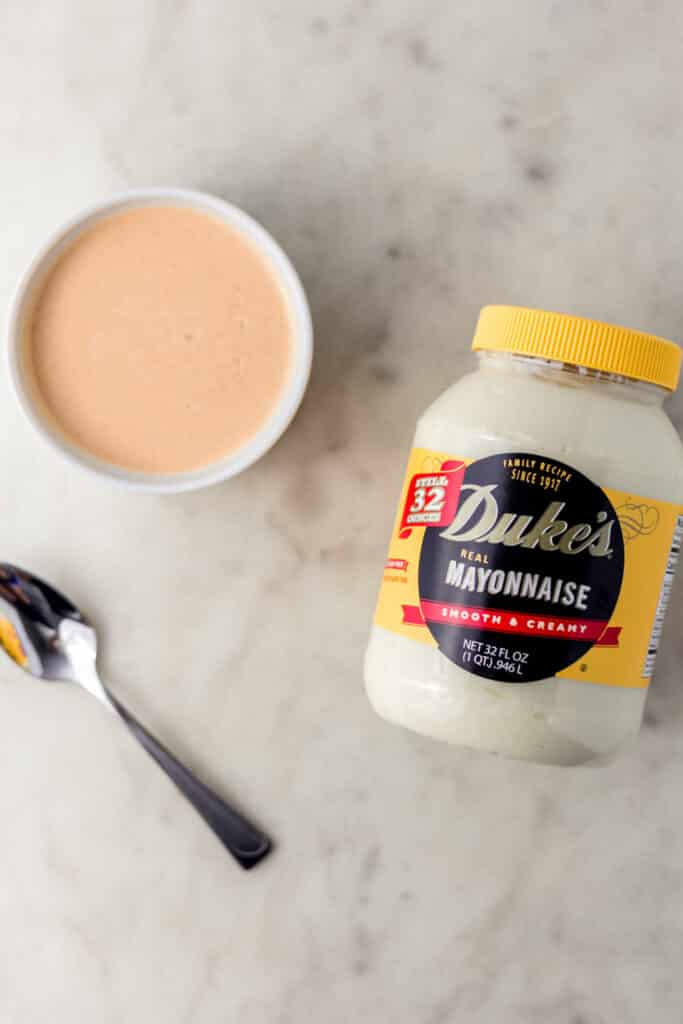 jar of Duke's Mayo next to spicy mayo mixture in white bowl and spoon