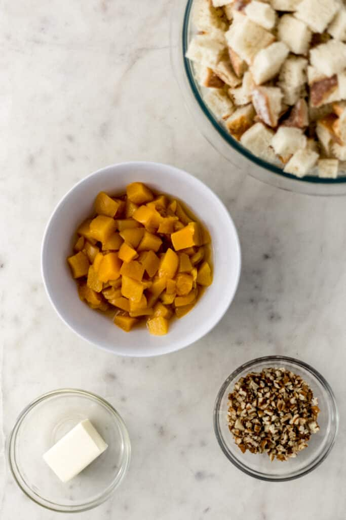 ingredients for peach bread pudding in separate small bowls