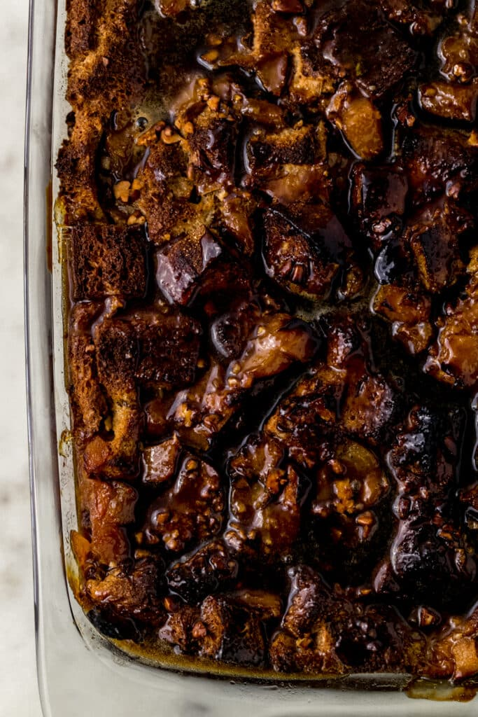 finished peach bread pudding in baking dish topped with brown sugar sauce