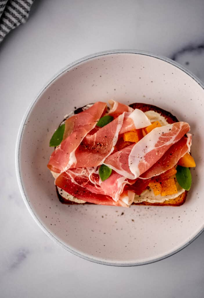 toast topped with prosciutto and peaches in white bowl