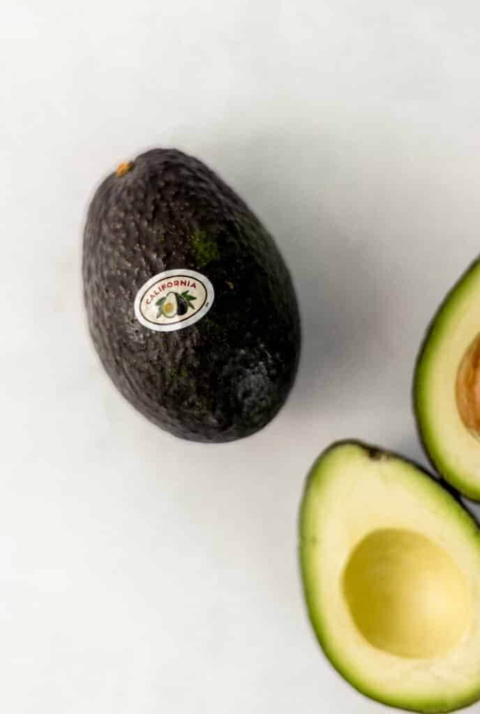 overhead view of fresh avocado with California sticker on it.,