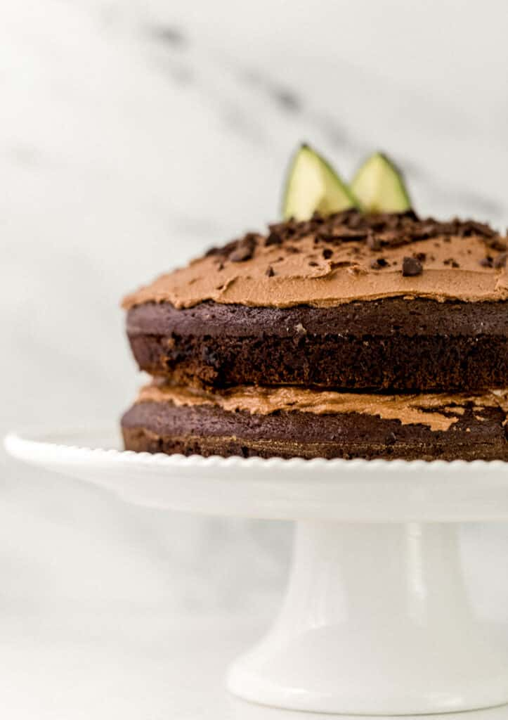 close up side view of frosted chocolate avocado cake on white cake plate.