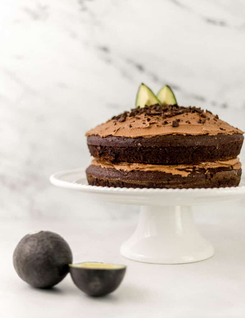 close up side view chocolate cake on white cake stand next to fresh avocados