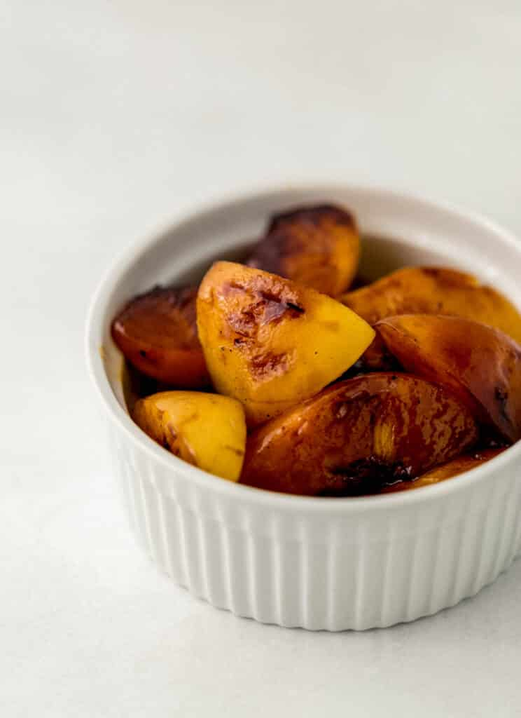 close up side view grilled peaches in white bowl.