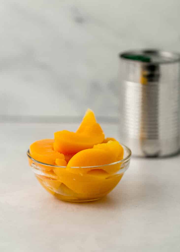 close up side view sliced peaches in small glass bowl