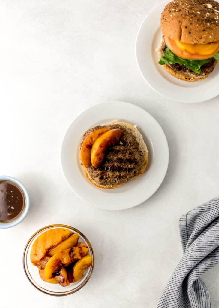 overhead view hamburgers on white plates with small bowl of grilled peaches.