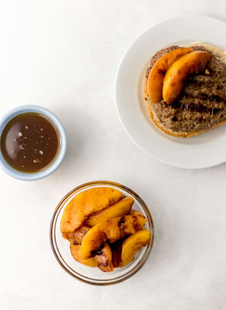 overhead view grilled peaches in glass bowl next to burger on white plate and sauce in a small bowl.