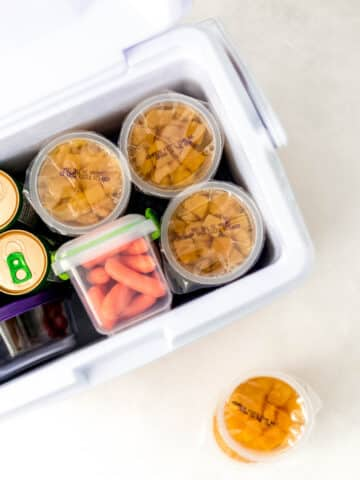 small cooler with snacks inside of it next to small containers of peaches