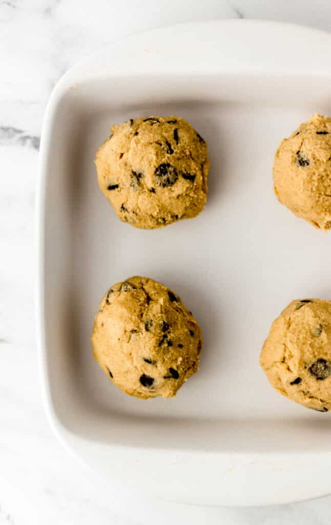 four balls of cookie dough in white square baking dish