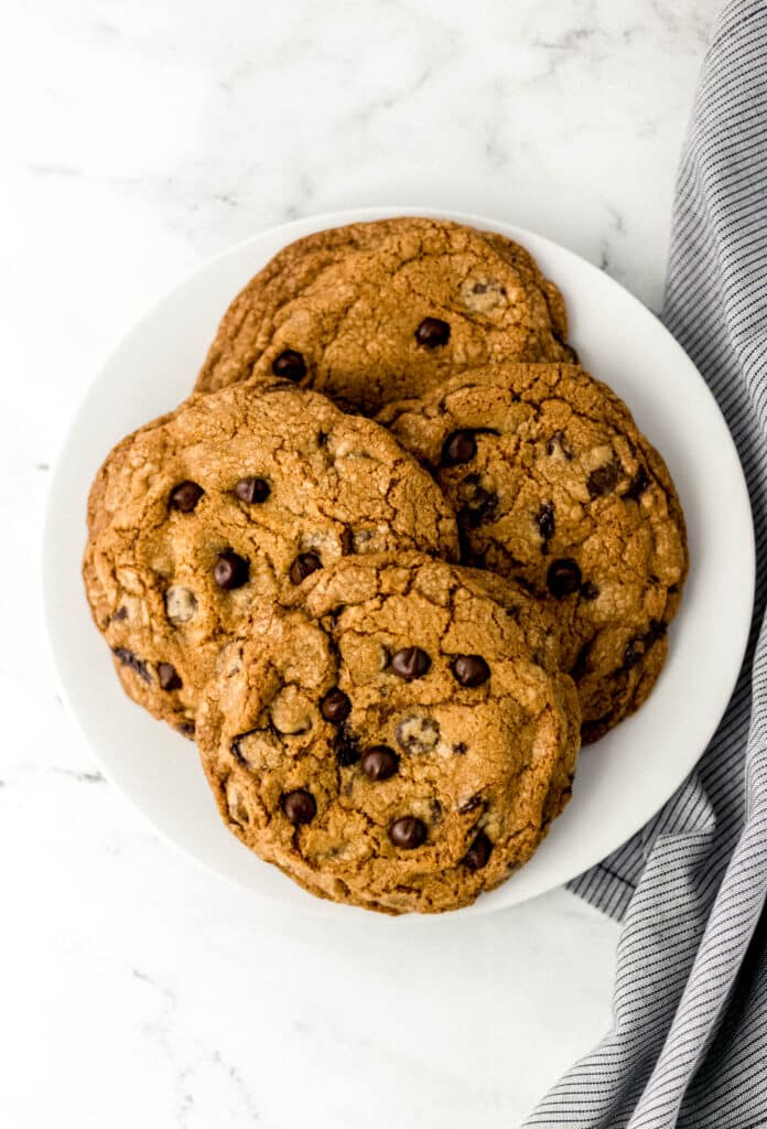 white plate with four large cookies on it beside cloth napkin on marble surface