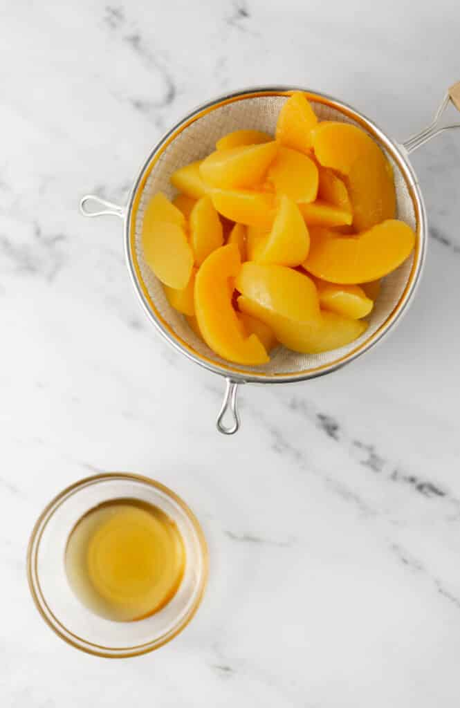 strainer with sliced cling peaches and small glass bowl with honey.